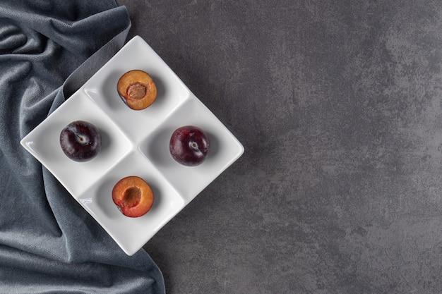 Fruits de prune rouge juteux entiers et tranchés placés sur une assiette blanche.
