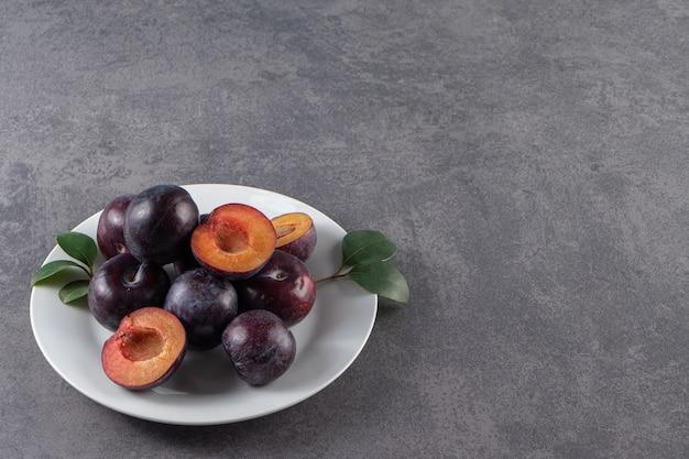 Fruits de prune rouge juteux entiers et tranchés placés sur une assiette blanche