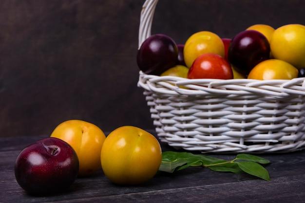 Fruits de prunes colorées dans le panier sur l'espace noir isolé