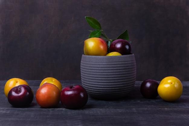 Fruits de prunes colorées en pot et plaque sur l'espace noir isolé