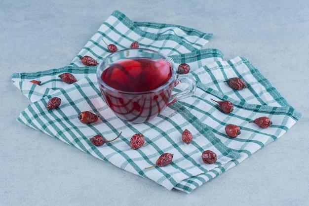 Fruits de rose musquée et thé sur serviette sur marbre.