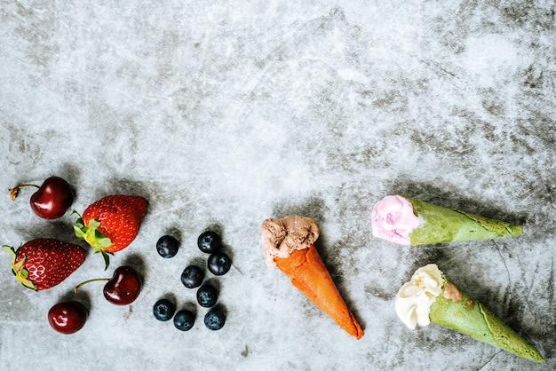 Fruits rouges comme les fraises cerises et les myrtilles à côté de trois glaces en cornet