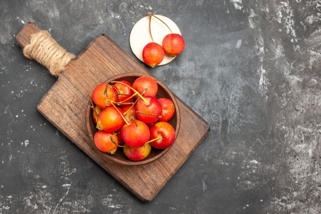 Fruits rouges frais de cerise dans un bol sur fond gris