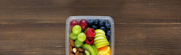 Fruits sains aux amandes dans une boîte à emporter sur fond de bannière en bois