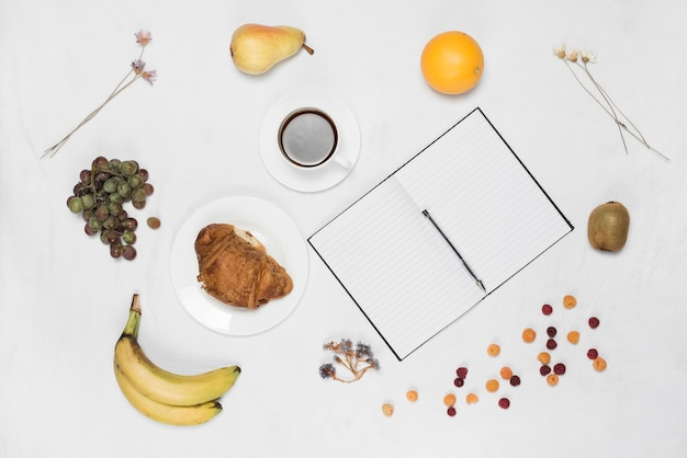 Fruits sains; café; croissant et stylo avec bloc-notes monoligne blanc sur fond blanc