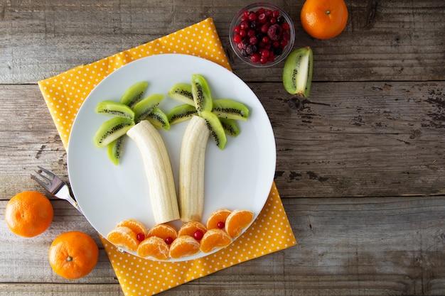 Fruits sains pour les enfants, banane kiwi et palmier mandarine.