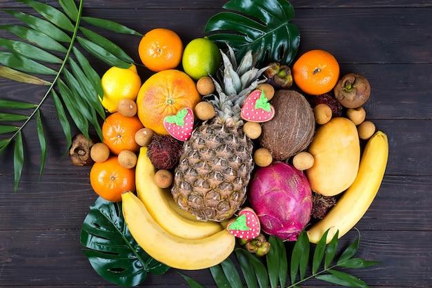 Fruits de saison d'été tropical tropical juteux sur feuille de palmier sur fond en bois