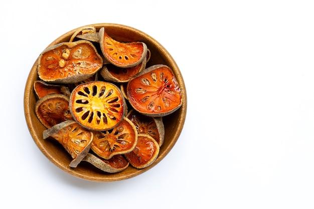 Fruits séchés bael dans un bol en bois sur blanc. vue de dessus