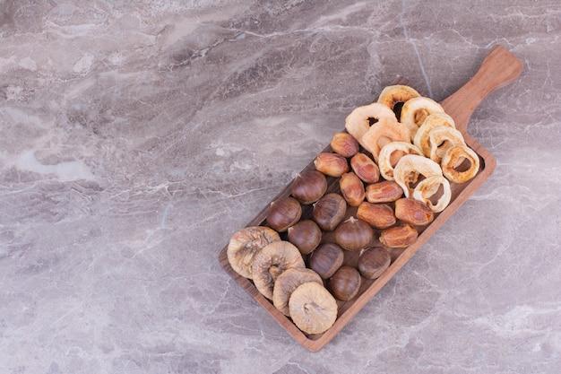 Fruits secs et baies sur plateau en bois.