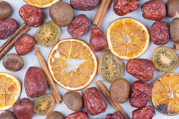 Fruits secs, bâtons de cannelle et châtaigne sur une surface en marbre.