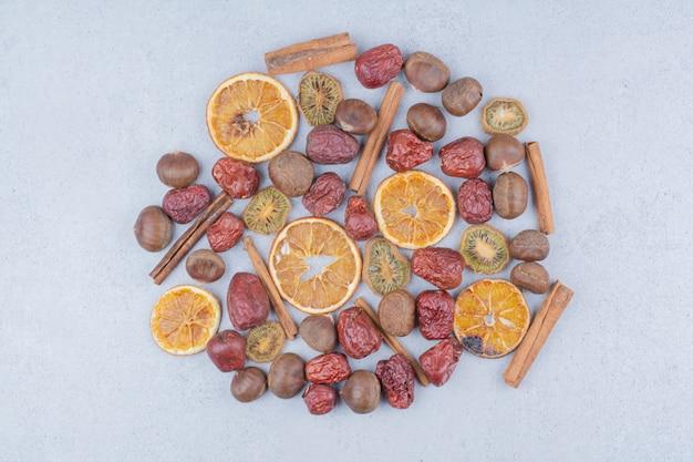 Fruits secs, bâtons de cannelle et châtaignes sur une surface en marbre.