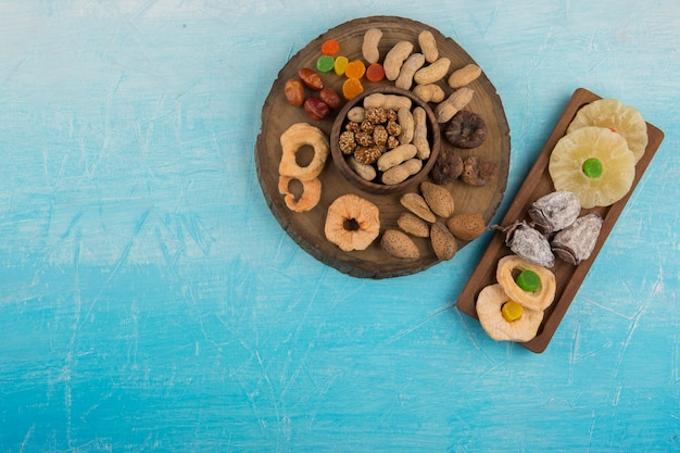 Fruits secs et collations dans des plateaux en bois sur la table bleue