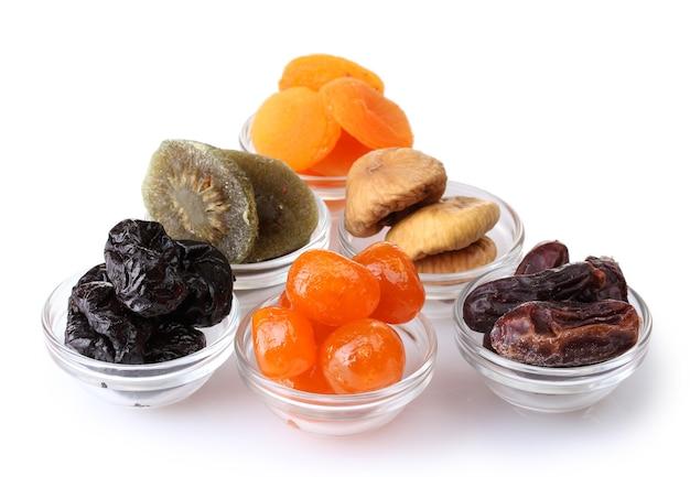 Fruits secs dans des bols isolés sur blanc