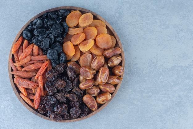 Fruits secs dans la planche de bois, sur la table en marbre.