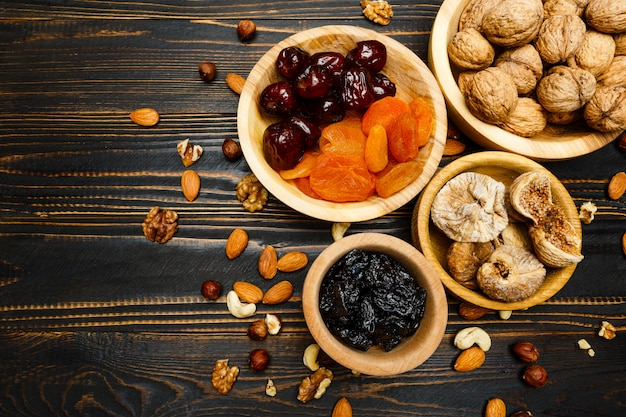 Fruits secs figues, abricots, prunes et noix sur table en bois