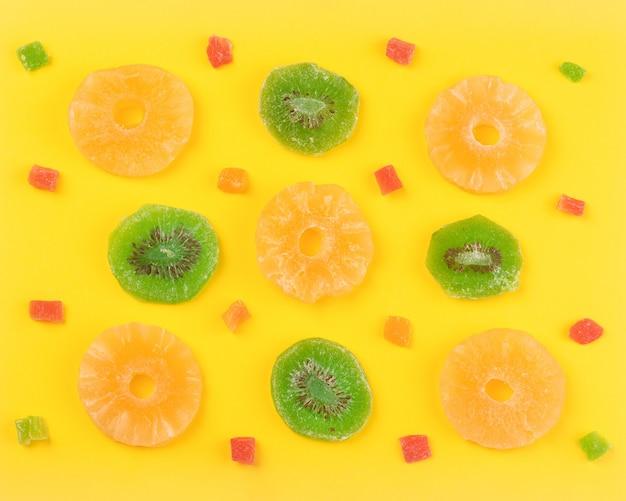 Fruits secs de kiwi et d'ananas près des fruits confits, fond coloré doux