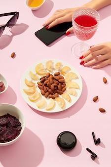 Fruits secs et noix avec sauce sur fond rose avec les mains de la femme