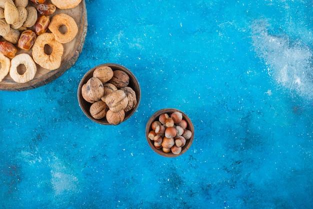 Fruits secs et noix savoureuses sur une planche, sur la table bleue.