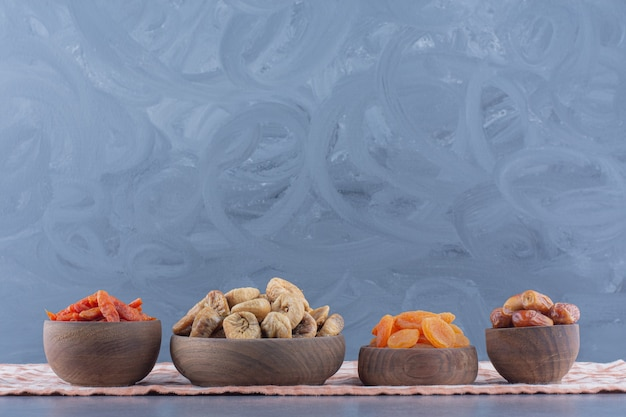 Fruits secs savoureux dans des bols sur la serviette, sur le fond de marbre.