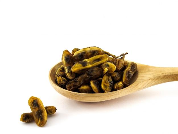 Les fruits secs de sophora japonica se trouvent dans une cuillère en bois sur fond blanc