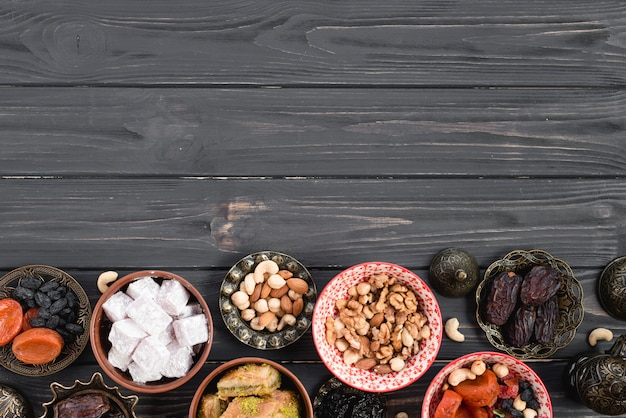 Fruits secs turcs frais; des noisettes; bonbons pour le ramadan sur un bureau en bois noir