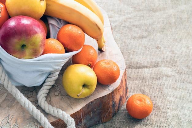Fruits sortant du sac en lin, debout sur une coupe en bois recouverte d'une toile de jute.