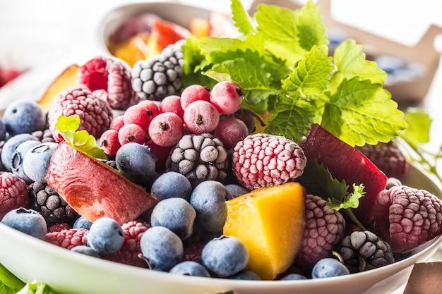 Fruits surgelés myrtilles mûre framboise groseille pêche et herbes mélisse.