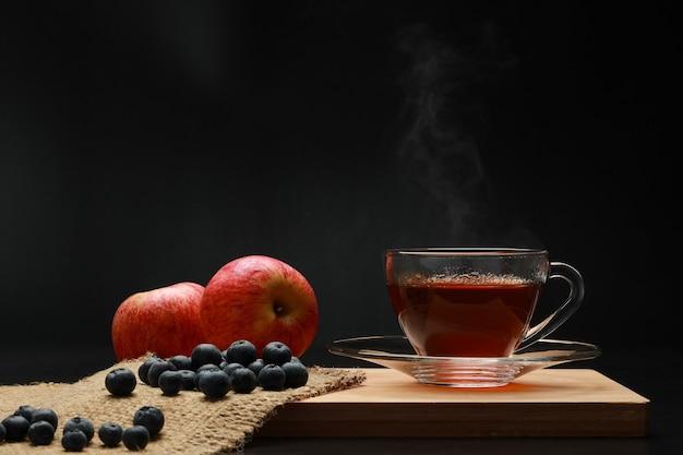 Les fruits de thé chaud dans une tasse en verre avec de la fumée et de la myrtille, pomme sur la planche de bois.