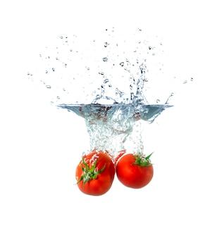Fruits tomates fraîches coulant dans l'eau