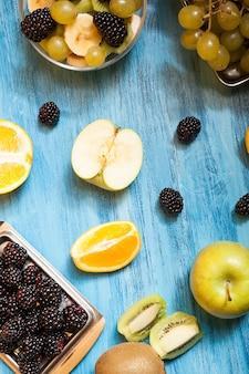 Fruits tranchés et barries sur un bureau bleu en studio. rafraîchissement naturel nutrition tropicale