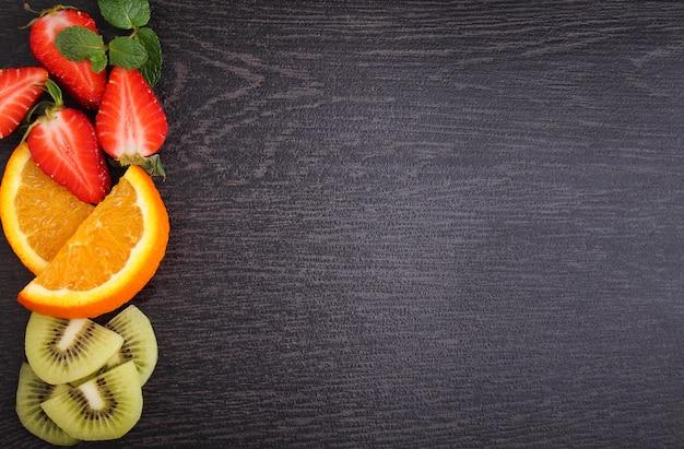 Fruits tranchés (fraises, kiwi, orange, banane) sur fond noir