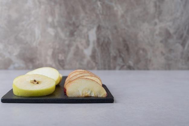 Fruits tranchés sur une planche à découper sur une table en marbre.