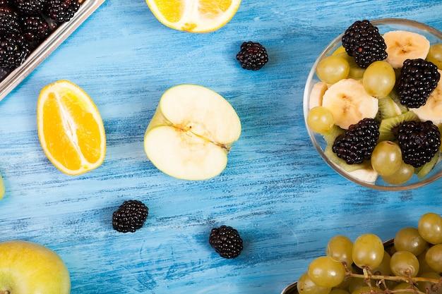 Fruits tranchés et vue de dessus de baies sur fond de bois bleu. une table en bois avec des fruits tropicaux frais. mélange de fraîcheur nature saine de fruits