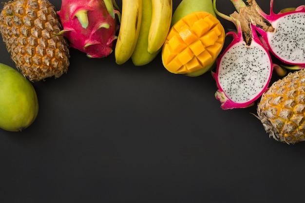 Fruits tropicaux ananas, banane, fruit du dragon et mangue sur fond noir. vue de dessus.