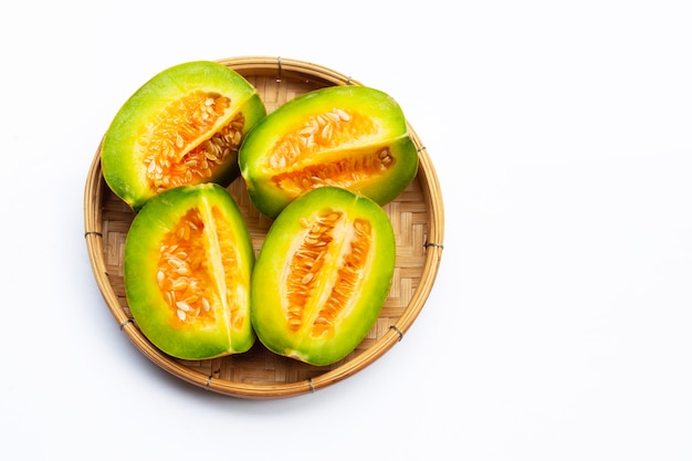 Fruits tropicaux, cantaloup thaï ou melon en tranches dans un panier en bambou sur blanc