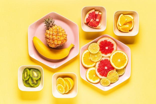 Fruits tropicaux entiers et tranches sur assiettes, vue de dessus.