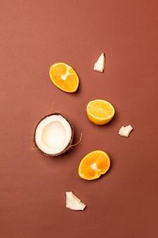Fruits tropicaux sur fond marron. morceaux de noix de coco, citron et orange. tropical plat poser.