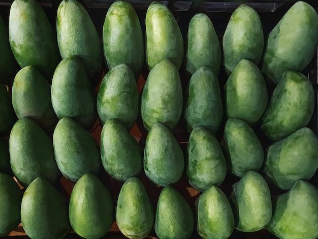 Fruits tropicaux. fond plein cadre de tas de mangues vertes fraîches.