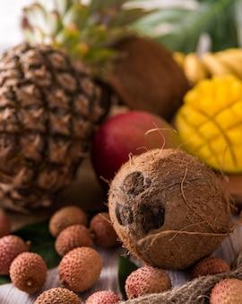 Fruits tropicaux frais sur la vue de dessus en bois. bananes, ananas, noix de coco, mangue, litchi, châtaignes. tonifié.