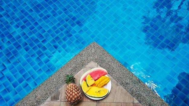 Fruits tropicaux juteux fixés au bord de la piscine avec de l'eau bleu cristal. repos de week-end de luxe