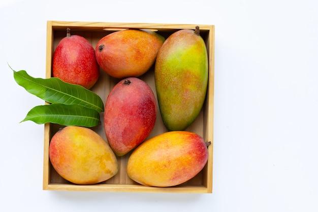 Fruits tropicaux, mangue avec des feuilles vertes dans une boîte en bois sur une surface blanche