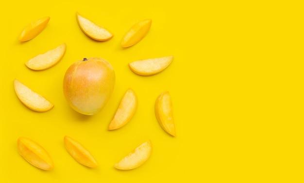 Fruits tropicaux, mangue sur fond jaune. vue de dessus