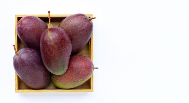 Fruits tropicaux, mangue fraîche dans une boîte en bois sur blanc isolé. vue de dessus avec espace copie