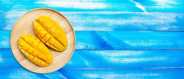 Fruits tropicaux, mangue en plaque de bois sur fond de bois bleu.