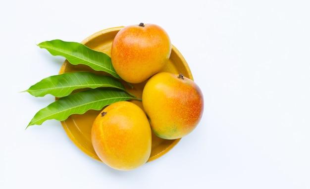 Fruits tropicaux, mangue sur plaque jaune sur surface blanche. vue de dessus