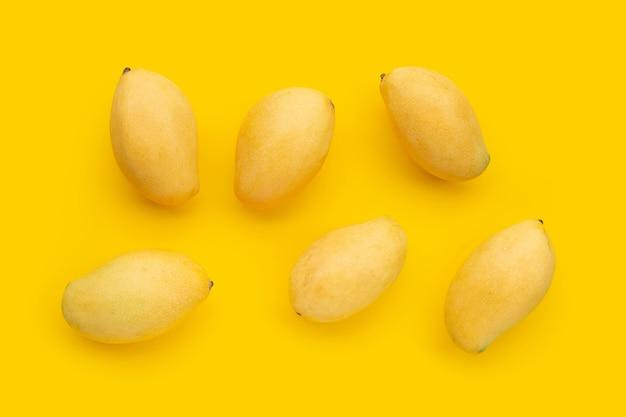 Fruits tropicaux, mangue sur surface jaune.