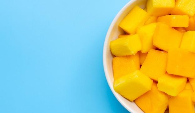 Fruits tropicaux, tranches de cube de mangue dans un bol blanc sur fond bleu.
