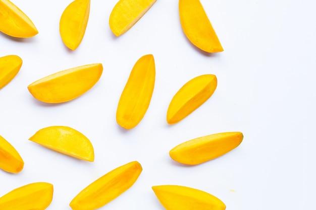 Fruits tropicaux, tranches de mangue sur blanc.