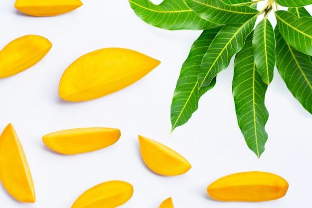 Fruits tropicaux, tranches de mangue avec des feuilles sur fond blanc. vue de dessus