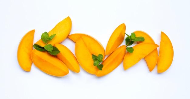 Fruits tropicaux, tranches de mangue avec des feuilles de menthe sur blanc.